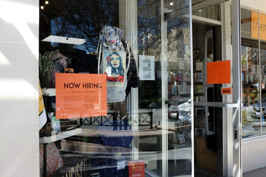 A+sign+on+the+window+of+boutique+store+Therapy+in+Mountain+View+reads+%22Now+Hiring.%22+Signs+like+this+have+popped+up+around+businesses+in+the+area+as+low-wage+workers+move+out+due+to+rising+housing+prices.+Mountain+View+has+increased+minimum+wages+at+an+accelerated+pace+to+combat+this+issue.+Photo+by+Michael+Sieffert.
