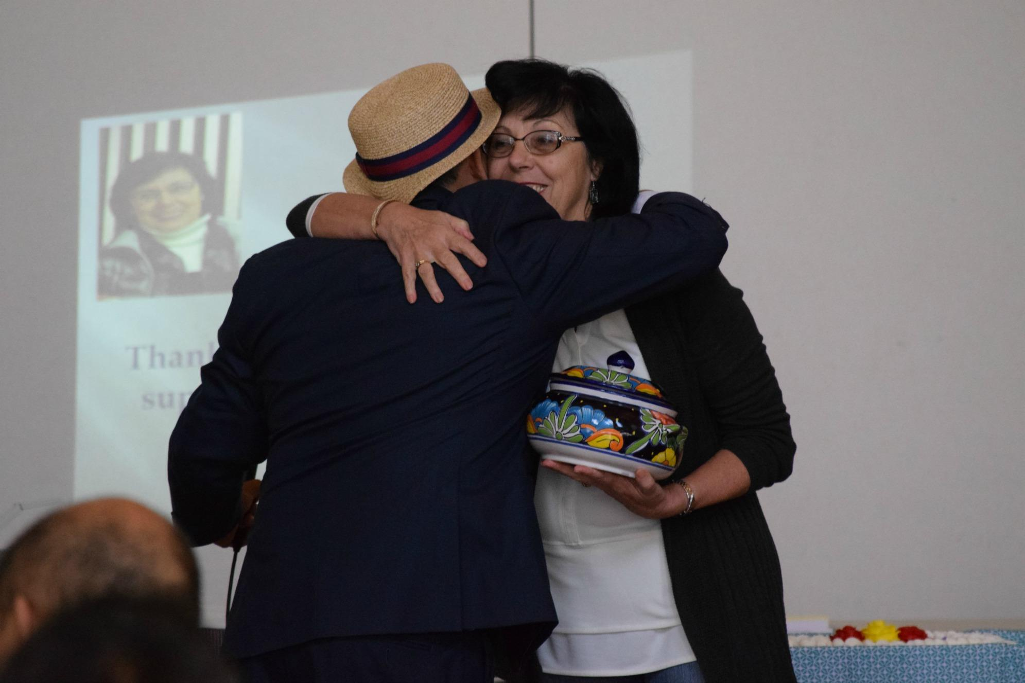 Former Associate Superintendent Brigitte Sarraf, who supported the Latino community during her 47 years with the district, receives a gift of appreciation from counselor Ariel Rojas during the Latino summit. Photo by Francesca Fallow.