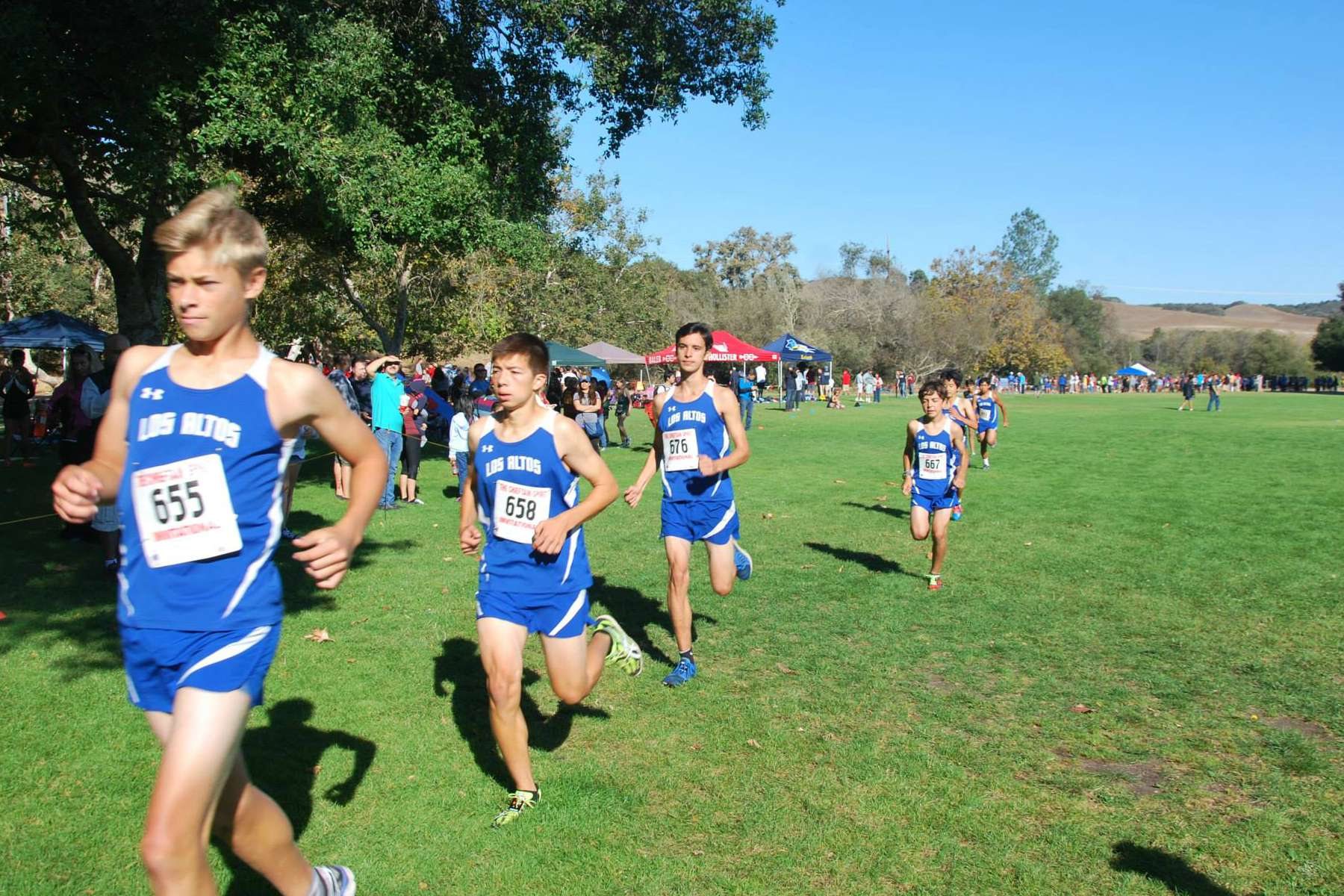 A stream of boys runners jog in a competition. The cross country team has been stressing a team mentality this season. Photo Courtesy Brian Wang
