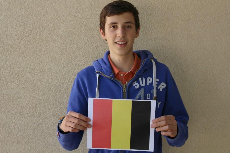 Senior Jens Tuyls poses with the flag of his home country, Belgium. Photo by Allegra Maeso.