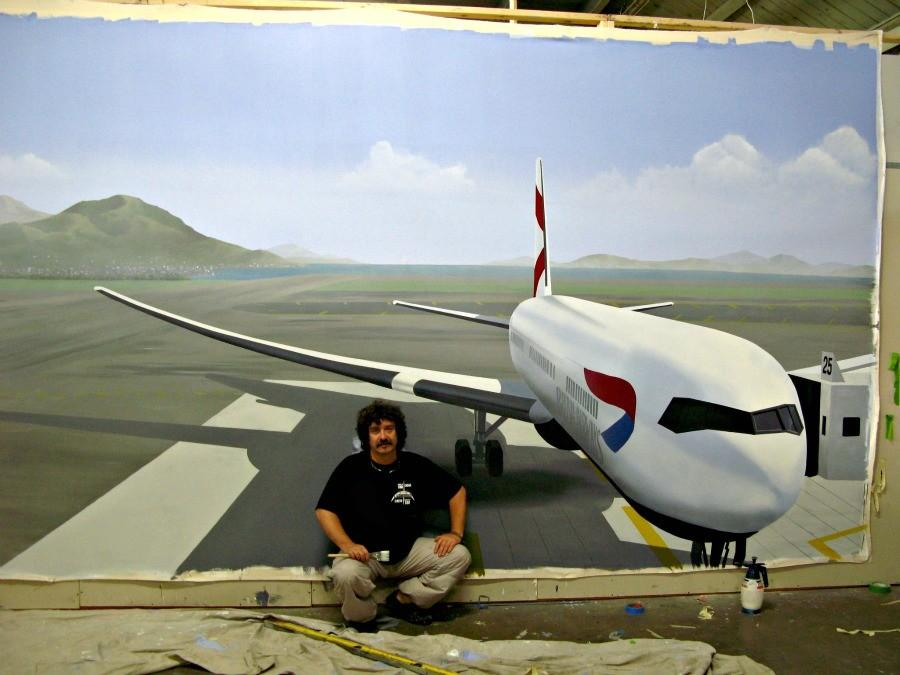Artist Andrew Johnstone poses with a trompe l'oeil style mural he painted at a Palo Alto pediatric dentistry in 2013. Photo courtesy Andrew Johnstone.