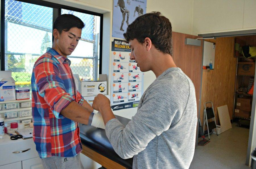 Junior Matt Ansari (right) treats an injured peer, junior Tamon Okura (left), after school. Photo by Kunal Pandit.