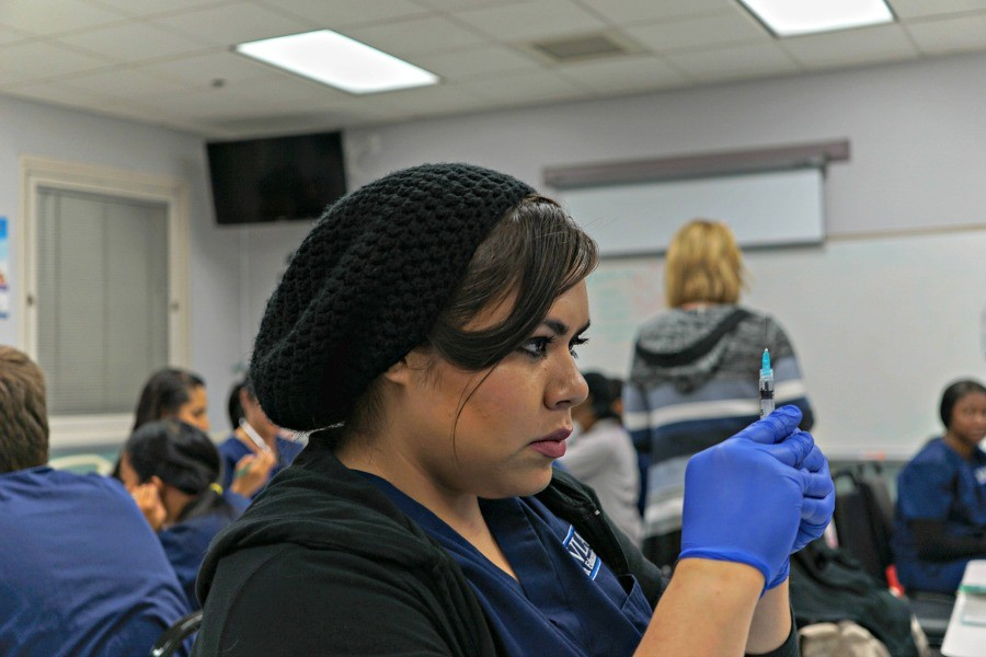 LAHS alumna Valeria Lopez '10 practices prepping a syringe for her Medical Assistant program. Photo by Michael Sieffert.