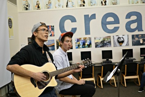 Juniors Viktor Niemiec (left) and Derek Mark (right) perform at the Open Mic Night in the library. Viktor sings and plays the guitar, while Derek beatboxes. Photo by Michael Sieffert.