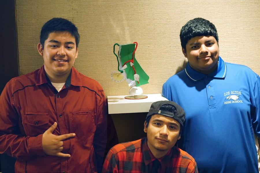 Juniors Ronaldo Flores, Martin Quezada and Luis Arias Diaz pose next to their artwork. The environmental science class's artwork is currently being featured in the