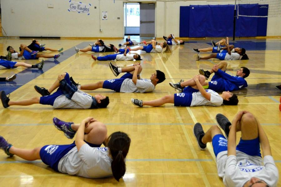P.E .students stretch during class. The P.E. department is planning to increase the amount of health awareness included in the curriculum in order to combat student stress. Photo by Katie Klein.