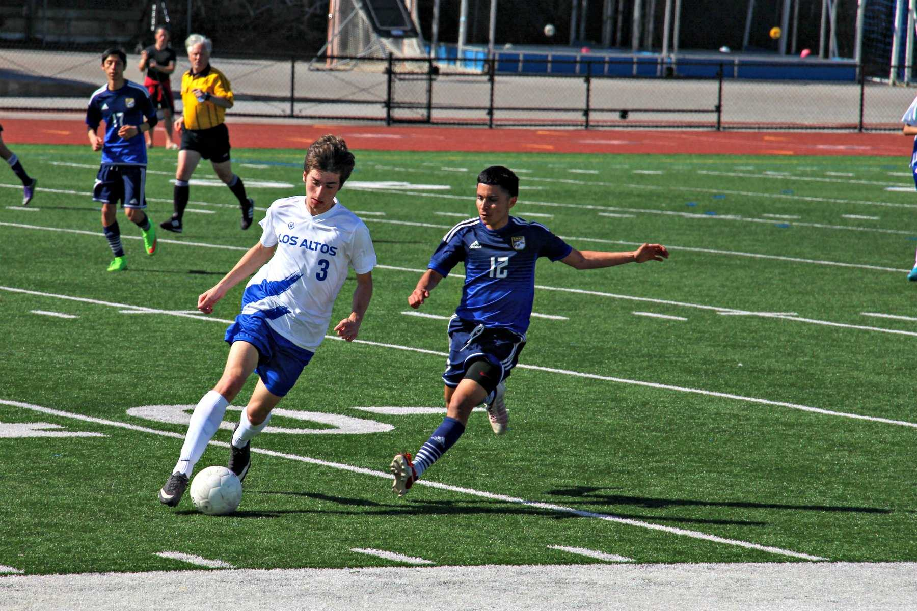 Senior Joe Kull dribbles the ball near a defender. Photo by Michael Sieffert.