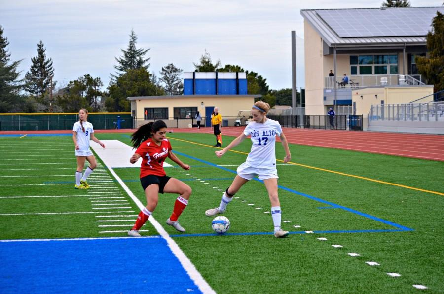 Senior Stephanie Kouvelas dribbles the ball near a defender. Photo by Kunal Pandit.