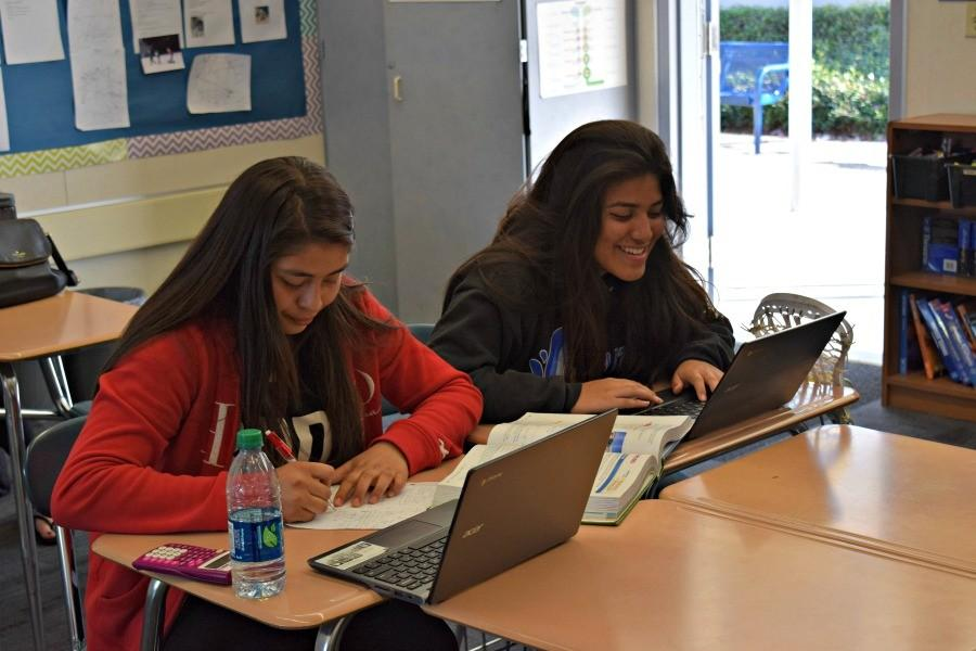 Sophomores Natalie Ramirez (left) and Odethe Virgen Barajas (right) study together during a free period. Both students are involved in the AVID and Skills classes tutoring program that pairs AVID student tutors with Skills students to help with homework after school three times a week. Photo by Francesca Fallow.