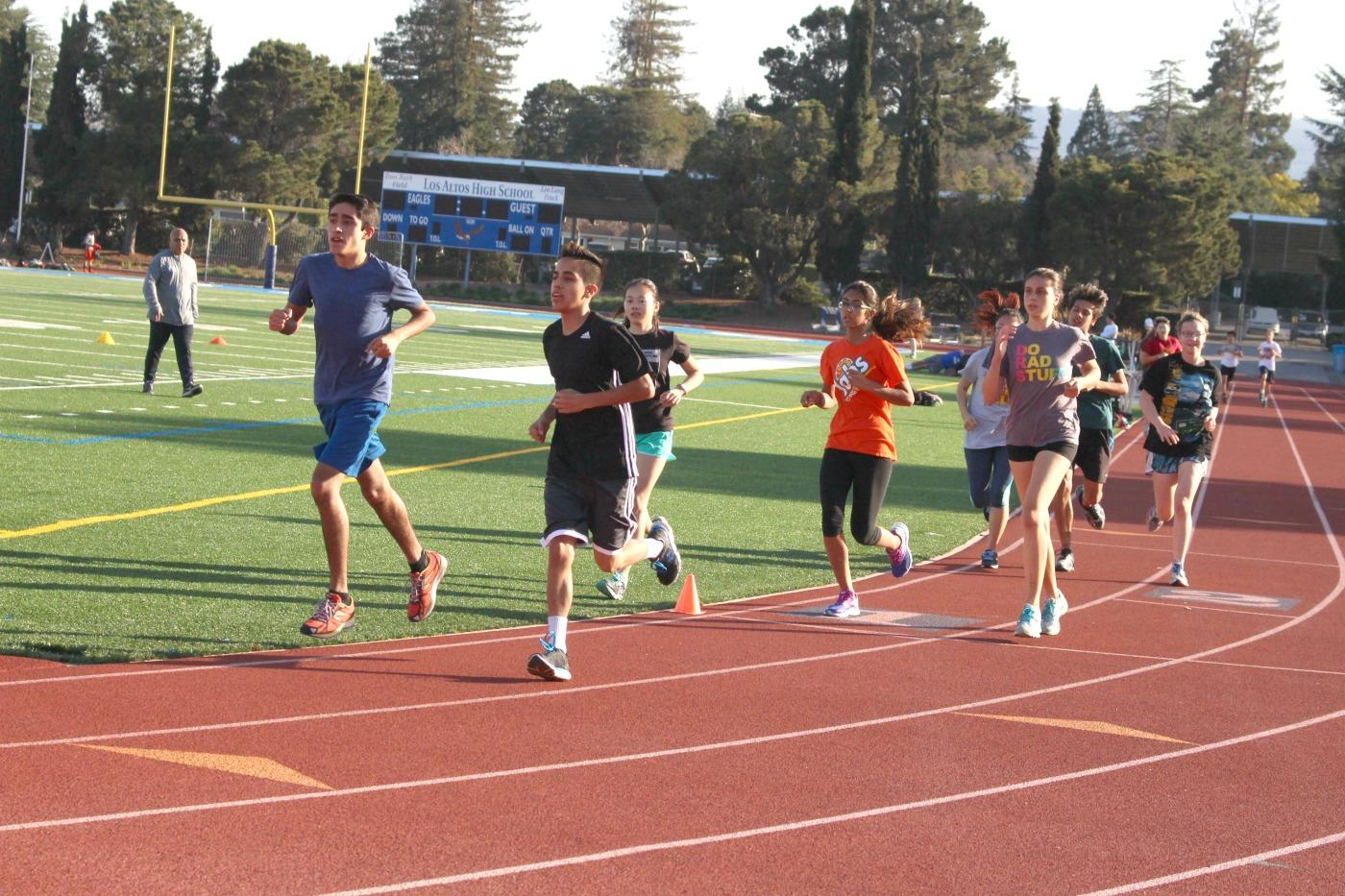 Members of the boys and girls track and field teams run laps during  practice. Both teams are optimistic for the coming season and are confident that they can achieve good results. Photo by Allegra Maeso.
