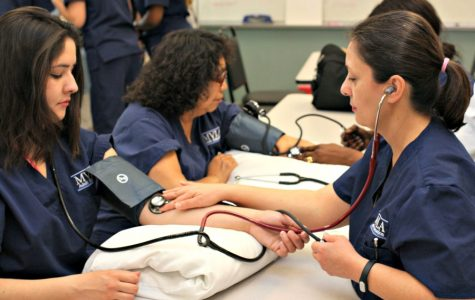 Teresa (left) practices taking blood pressure and pulse with a peer. While still a student at LAHS, Teresa attends nursing classes and holds a part time job. Photo courtesy Teresa Casillas.