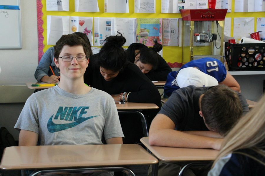 Senior Chris Carter meditates in Film Analysis while students color in zen coloring books and meditate around him. Film Analysis teacher Susana Herrera began the