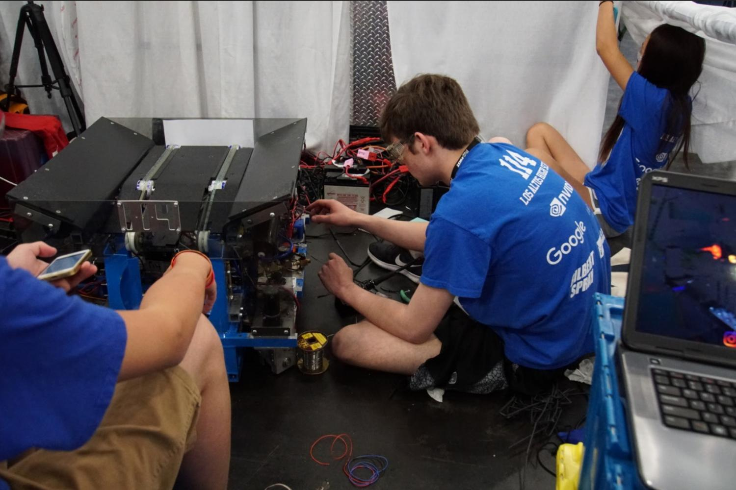 Drive+team+members+Cole+Brinsfield+%28middle%29+and+Michelle+Zhu+%28right%29+race+to+fix+the+wiring+on+their+robot%27s+drivetrain.