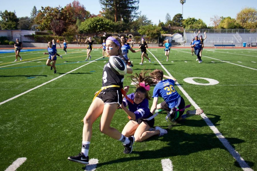 Evelyn+Baher-Murphy+dodges+around+two+freshmen+and+makes+her+way+up+the+sideline+in+Friday%27s+Girls+Flag+Football+final.