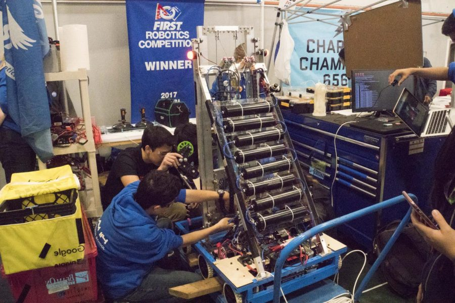 Team members junior Nick Borda (bottom left) and senior Drake Moore (center left) work on the elevator system after a malfunction on the second day of the Ventura Regional. The team finished in semifinals despite a delayed build season that pushed back coding and driving practice. Courtesy Ryan Cardona.
