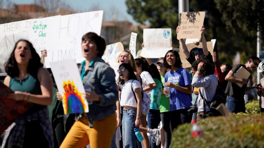 Students chant and hold signs as they walk to Wells Fargo in downtown Los Altos.