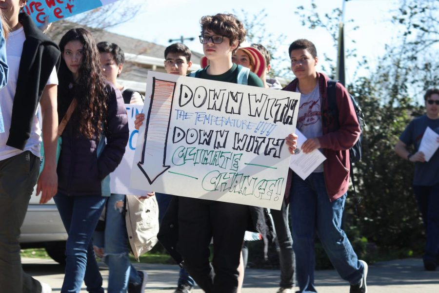 One student holds a poster that reads,
