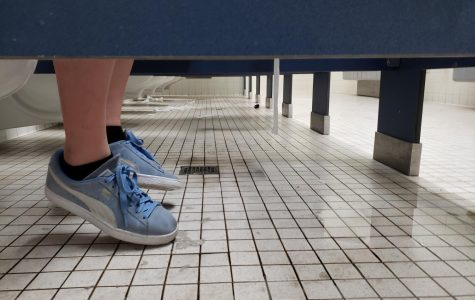 Isabella Borkovic hesitates to place her shoes on the dirty and wet bathroom floor.