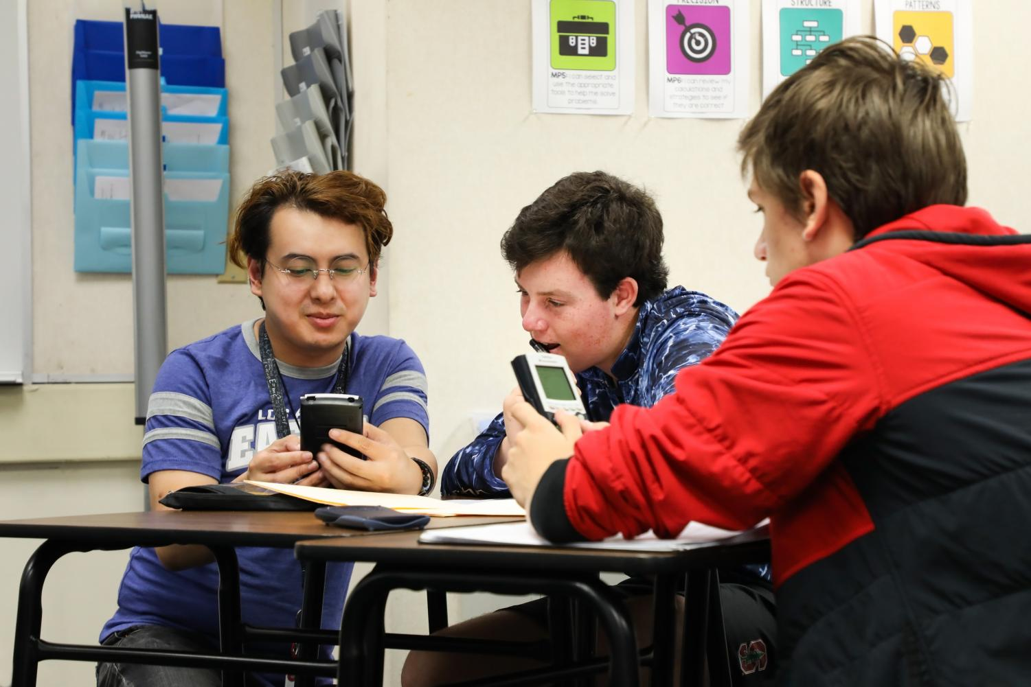 In second period Calculus BC class, math teacher Victor Nguyen teaches juniors Grady Hofmann and Egor Cherkashin how to compute and graph derivatives on their calculators.
