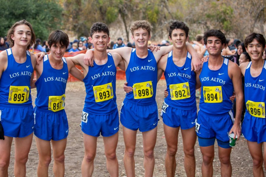 Sage and Cohan (second and third to the left, respectively) pose with the Los Altos varsity boys cross country team in Woodward Park after the 2019 CIF-States Cross Country Championships. At this meet, the boys team broke the school course record for the third year in a row.