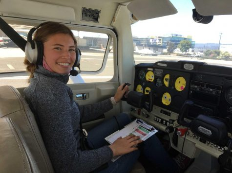 Senior Kate Koralevskaya sits in the cockpit of a plane at San Carlos Airport awaiting the beginning of her flight training. Many of the flight instruments are covered with emoji stickers to ensure focus on her surroundings. Over the summer, she learned how to fly and obtained her private pilot's license through the Upwind Scholarship.