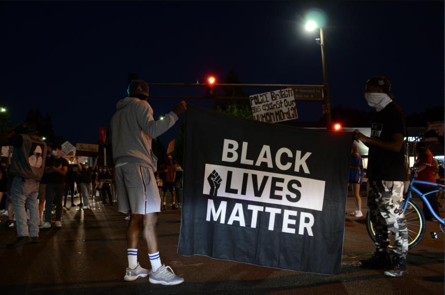 Protestors carry a BLM banner.