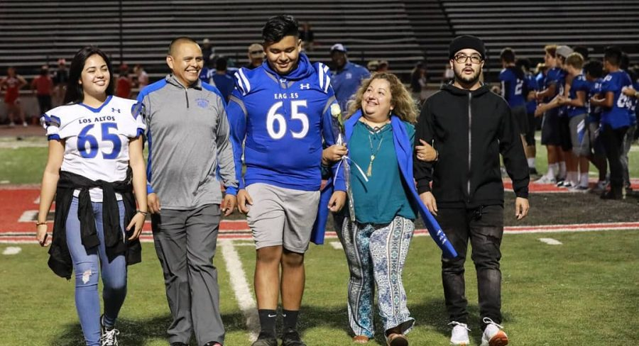 Miguel Orozco, '20, (third from the left) is pictured walking down the Foothill College football field with his family during the 2019 LAHS Homecoming game. Orozco is starting his freshman year at Foothill College virtually this fall to complete EMT training in hopes of becoming a firefighter in the future.