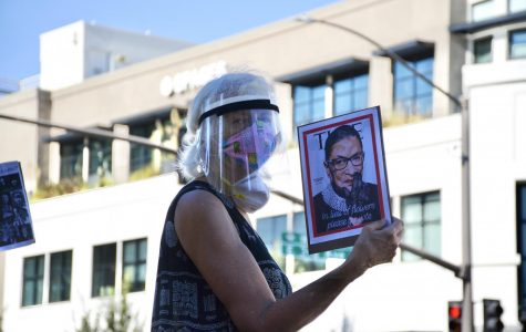 A protester honors the late Ruth Bader Ginsburg. At today's rally in San Mateo, many held picket signs denouncing Donald Trump and Amy Coney Barrett.