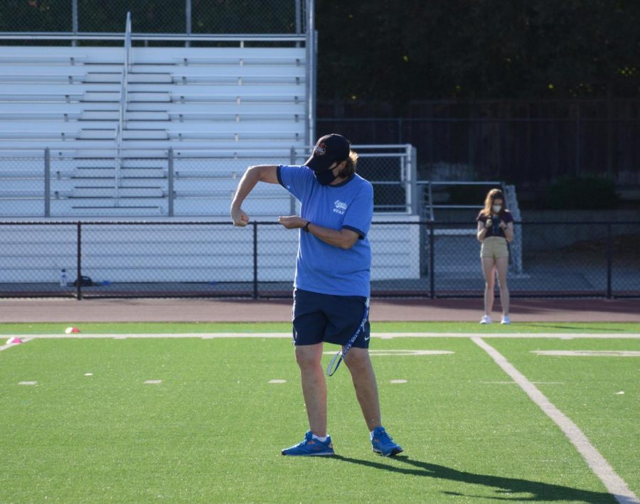 Varsity field hockey coach Mary Donahue demonstrates a stick skill to her practice cohort. With the transition to in-person practices during the COVID-19 pandemic, only 14 athletes per coach are allowed, masks must be worn when players are not engaging in strenuous activity and social distancing rules are required.