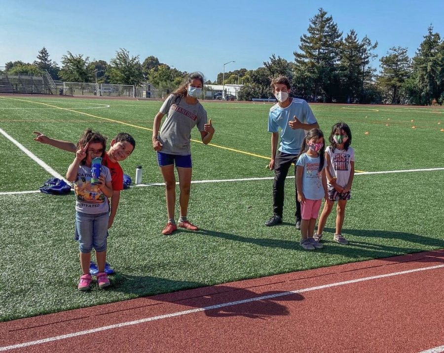 Juniors Allan Feldman and Esha Gupta pose with kids attending their sports clinic, AE Soccer Training. After seeing sports camps shut down due to the COVID-19 pandemic, four LAHS students decided to create safe sports clinics to benefit young athletes around the Bay Area.