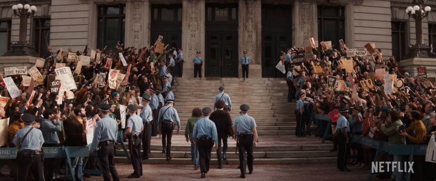 Police escort one of the Seven to the courthouse, surrounded by protesters. The movie 'The Trial of the Chicago Seven' highlights parallels between the 1960s and the present.