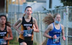 Freshman Maddy Randall (right) pushes ahead of Mountain View High School runners in the varsity girls race. She finished sixth in her race and 13th overall out of 111 varsity girls.