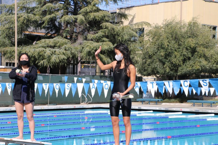 Senior May Jiang waves to her teammates as she is recognized at the last swim and dive meet of the season. After a close virtual competition against Gunn High School and Homestead High School, the team was able to relax and enjoy their final moments together.