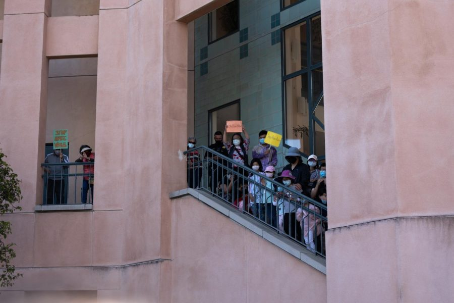 Crowds gather on the stairwell overlooking speakers at City Hall.