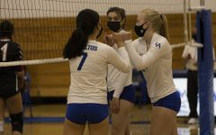 Two Los Altos volleyball players share a forearm bump in celebration during their first match of the 2021 season against Gunn. Despite COVID-19 restrictions, the team has found ways to maintain team spirit.
