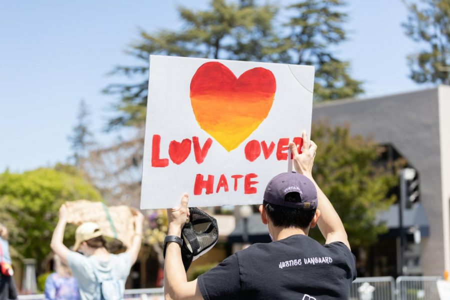 A Protester holds a sign while marching through downtown Mountain View.