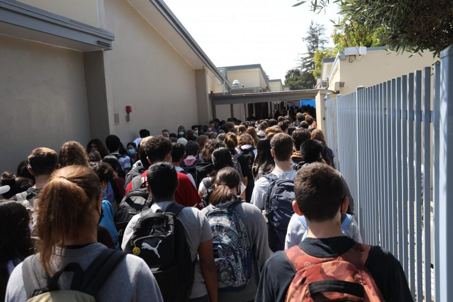Students walk to and from the 600-wing building through a single hallway between the campus pool and 500-wing buildings, and are seen packed together in the student traffic.